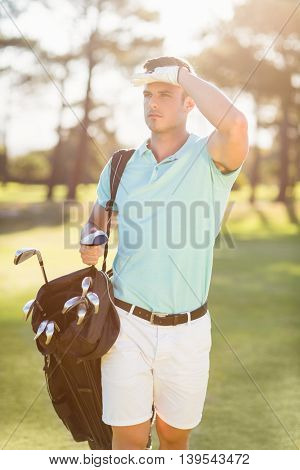 Golfer shielding eyes while standing on field
