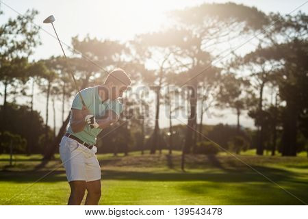 Male golfer taking shot while standing on field