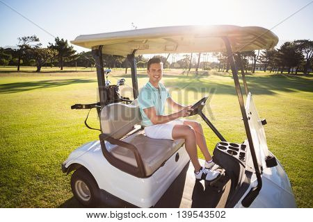 Full length portrait of man sitting in golf buggy on sunny day