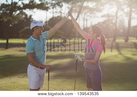 Smiling golf player couple giving high five while standing on field