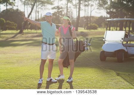 Smiling golf player pointing while standing by woman on field