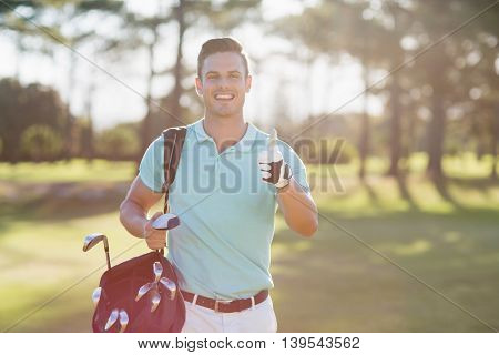 Portrait of smiling golfer man showing thumbs up while standing on field