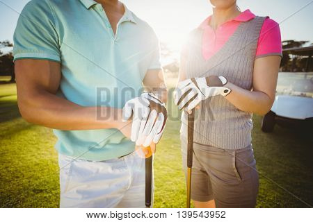 Midsection of golfer couple standing on field
