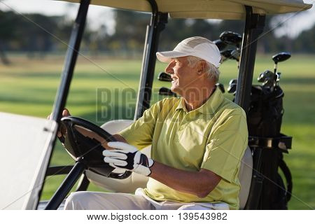 Smiling mature man driving golf buggy on field