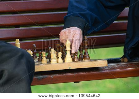 Old friends and free time. Two seniors having fun and playing chess game at park on bench.