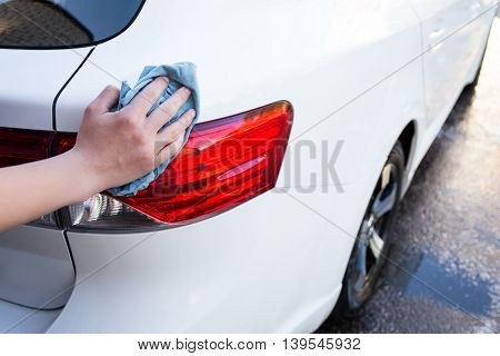 Close Up Of Male Hand Washing Car Lights With Microfiber Cloth