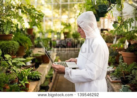 Side view of male scientist in clean suit using laptop at greenhouse