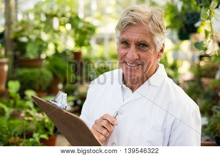 Portrait of confident senior male scientist holding clipboard while standing at greenhouse
