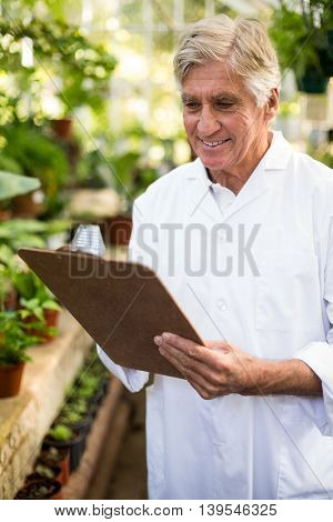 Senior male scientist smiling while writing on clipboard at greenhouse