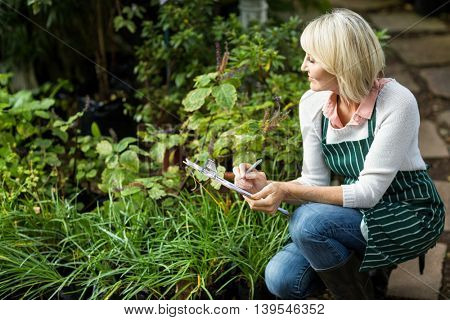 Woman writing on clipboard while examining plants at greenhouse