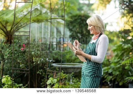 Side view of woman smiling while writing in clipboard outside greenhouse