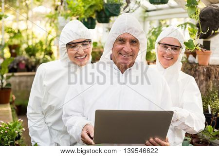Portrait of happy coworkers in clean suit with laptop at greenhouse