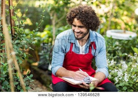 Smiling male gardener writing on clipboard while sitting at greenhouse