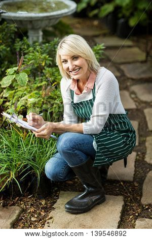 Portrait of happy woman writing on clipboard while examining plants at greenhouse
