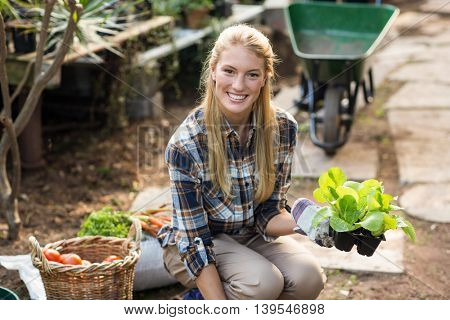 Portrait of happy female gardener holding sapling outside greenhouse