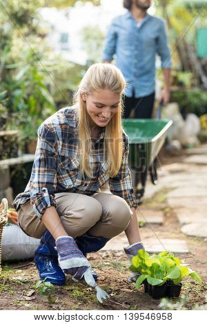 Female gardener planting while man working in background outside greenhouse