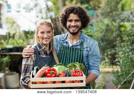Portrait of happy couple holding vegetables crate outside greenhouse