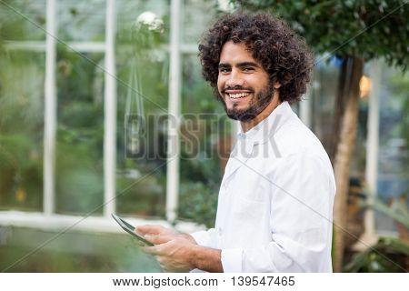 Portrait of happy male scientist using digital tablet outside greenhouse