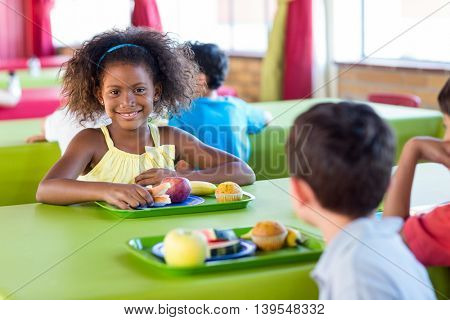 Portrait of smiling girl with classmates having meal in canteen