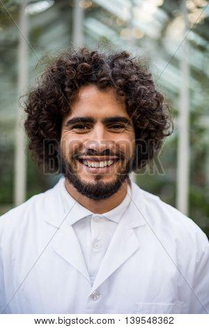 Portrait of confident male scientist standing against greenhouse