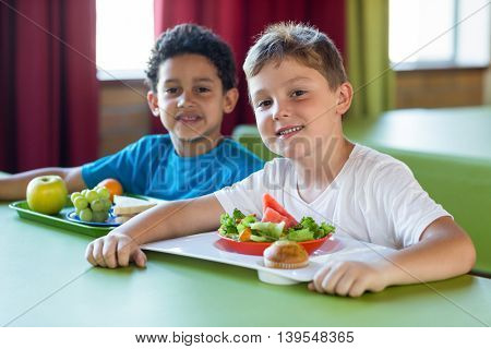 Portrait of smiling schoolboys having meal in canteen