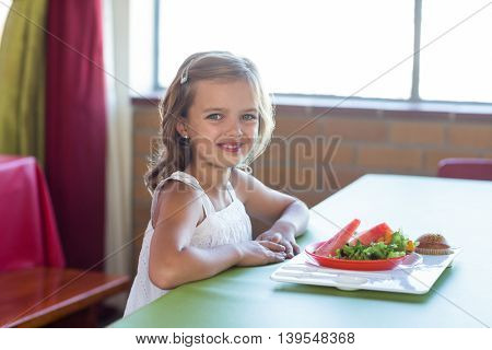 Portrait of smiling girl having meal in canteen
