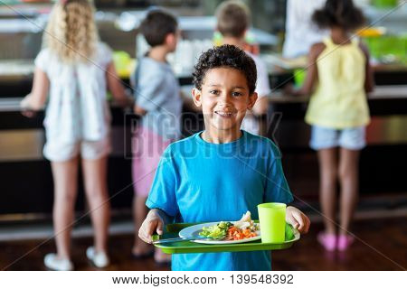 Portrait of happy schoolboy holding food tray in canteen against classmates