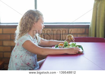 Smiling cute girl having meal in canteen