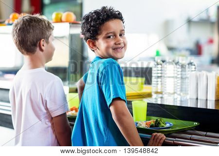 Portrait of smiling schoolboy with classmate standing near canteen counter