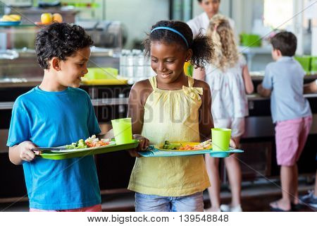 Smiling schoolchildren holding food tray in canteen against classmates