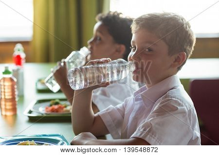 Portrait of schoolboy drinking water from bottle in canteen by classmates