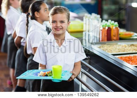 Portrait of cute schoolgirl with classmate standing near canteen counter