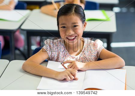 Portrait of smiling girl writing on book in classroom