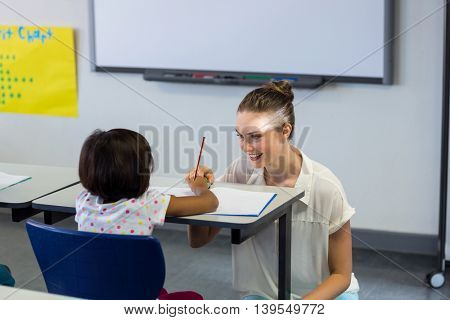 Smiling female teacher kneeling by schoolgirl in classroom
