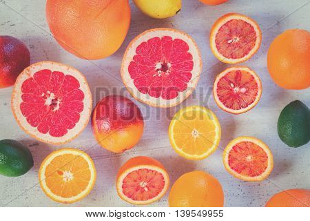 Mix of whole an cut citruses on white table, top view, retro toned