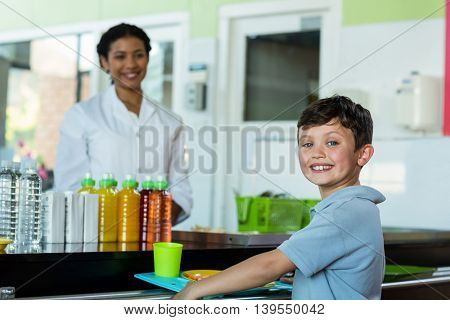 Portrait of smiling woman with schoolboy standing at canteen counter