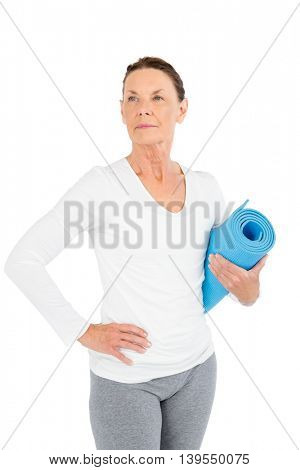 Mature woman holding exercise mat while standing on white background