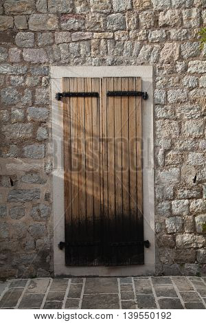Wooden door in old town in Montenegro. House made of bricks with vintage entrance.