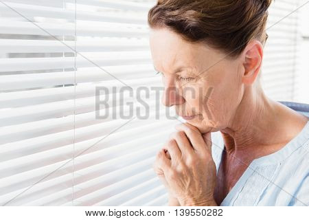 Close-up of thoughtful mature woman with hand on chin