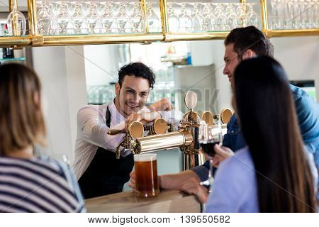 Friends talking to barkeeper while having drinks at counter in bar