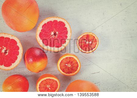 Mix of whole and cut citruses with copy space on white wooden table, retro toned