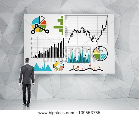 Businessman in dark suit standing in front of wall with various charts on it. Concept of thinking analyzing and decision making