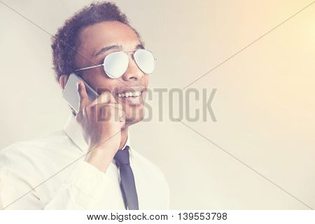 Portrait of young african american guy in glasses having a mobile phone conversation on light background. Toning filter