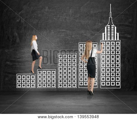Two businesswomen drawing and climbing abstract city ladder leading to tall tower on chalkboard background. Success concept