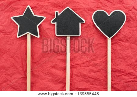 Sign star house heart lie on the red crumpled paper with place for your text
