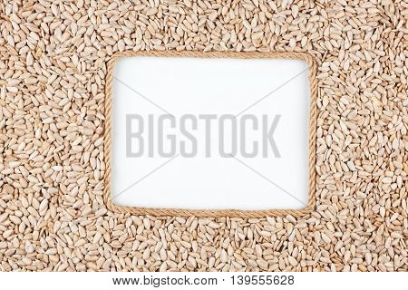 Frame made of rope with sunflower seeds and a white background with space for your text