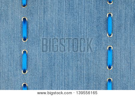Blue satin ribbon inserted in the gold rings on denim with space for your text