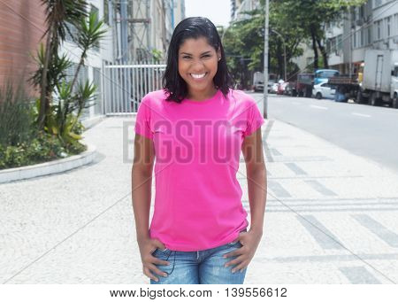 Walking native latin woman in a pink shirt in city in the summer