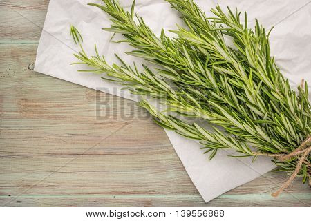 Bunch of rosemary on old wooden board. Top view with copy space