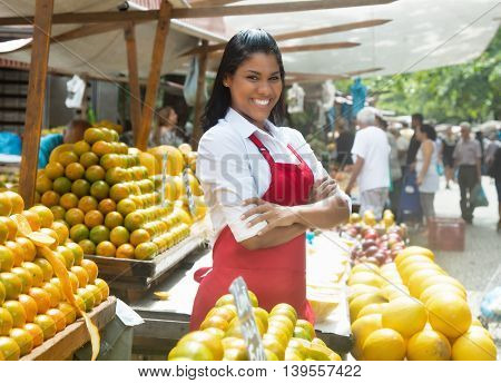 Beautiful mexican saleswoman with oranges outdoor on a farmers market
